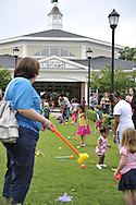 Families playing croquet at Historic Nunley's Carousel Centennial Celebration on Saturday, June 9, 2012, at Museum Row, Garden City, Long Island, New York, USA. Players used colorful plastic mallets to hit balls through hoops decorated with carousel horses at the 100th Anniversary festivities.