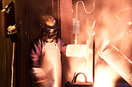 Pacific Steel Casting Company employee pours molten alloy from one bucket to a smaller bucket