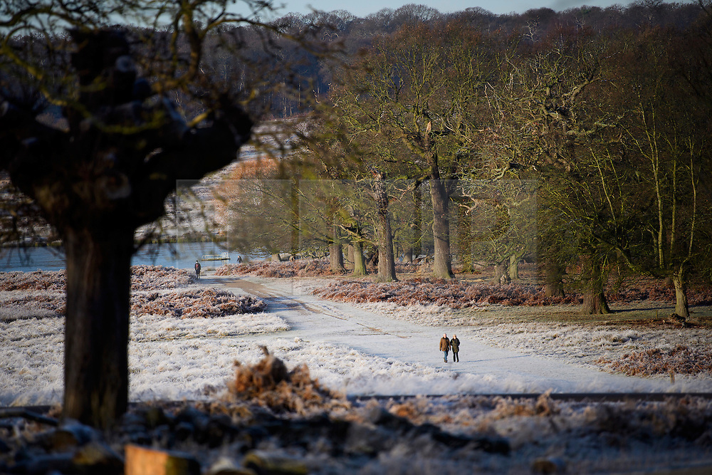 © Licensed to London News Pictures. 03/01/2017. London, UK. A couple walk through a frost covered landscape in Richmond Park in London as temperatures in the capital drop below zero. . Photo credit: Ben Cawthra/LNP