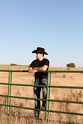 cowboy leaning on a fence outdoors