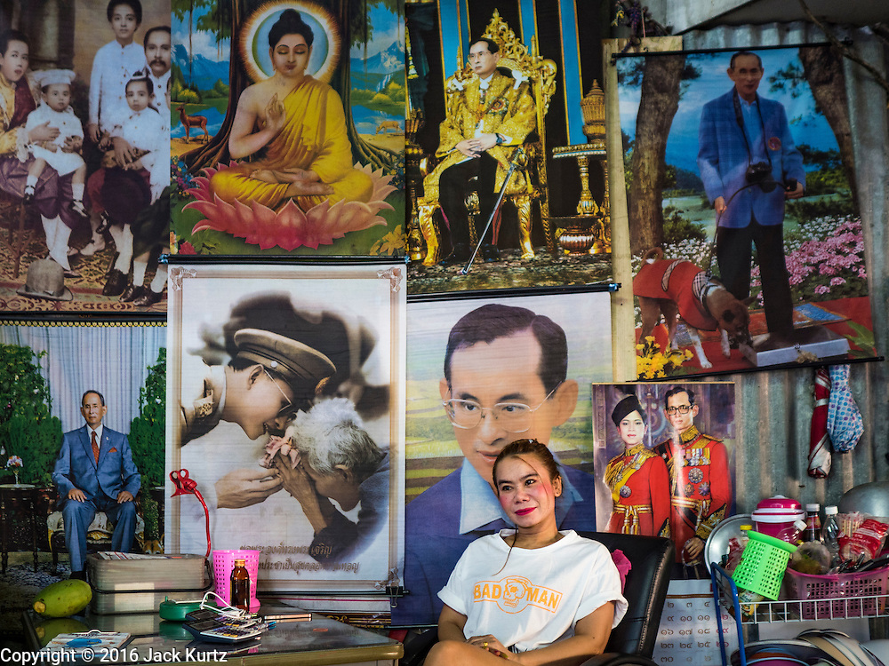01 DECEMBER 2016 - BANGKOK, THAILAND:  A woman in a market in Bangkok sits along a wall decorated with photos of Bhumibol Adulyadej, the Late King of Thailand, who died on Oct 13. Thailand's parliamentary body, the National Legislative Assembly, invited HRH Crown Prince Maha Vajiralongkorn to be king following the death of the Crown Prince's father, Bhumibol Adulyadej, the Late King of Thailand. The invitation marked the formal beginning of the process of naming the new King, although Crown Prince Vajiralongkorn was the heir apparent and Bhumibol's appointed successor. Shops that sell royal paraphernalia are now selling new portraits of  Crown Prince Vajiralongkorn which will be displayed alongside portraits of his late father.     PHOTO BY JACK KURTZ