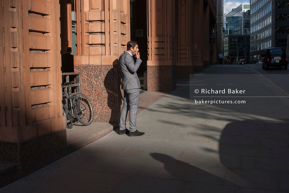 A businessman on a cigarette break smokes outside offices in late summer sunshine in the City of London, England UK.