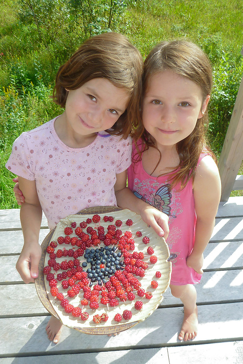 Two young girls show off their berry picking decoration in Gustavus.