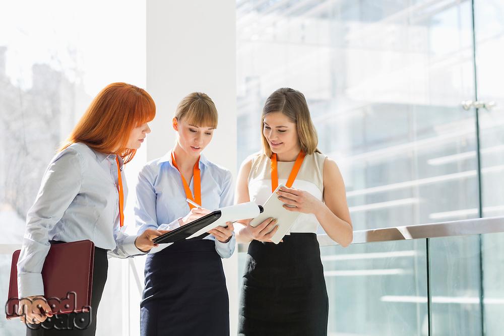 Businesswomen doing paperwork by railing in office