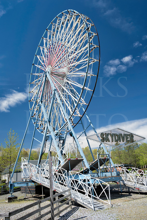 Reaching for the blue skies of Spring, this amusement park ferris wheel waits for another summer season of mild thrill seekers looking for a little fun. The gondola cars haven't been installed from winter storage yet, so the Skydiver waits in the sun.