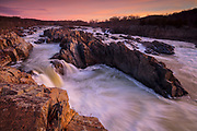 Under a red sunrise, the Potomac River drops 76 feet (23 meters) in a series of rapids at Great Falls Park, Virginia. Great Falls and the Potomac River are located within the state of Maryland, but the main section of the park and the viewing decks are in Virginia.
