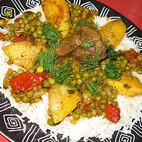 Lamb stew with potatoes, tomatoes, green peas, turmeric, olive oil, and fresh dill over white rice - Middle Eastern Food.