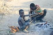 Africa, Tanzania, Lake Eyasi, A Hadza child playing a rebab a single-string bowed lute April 2006