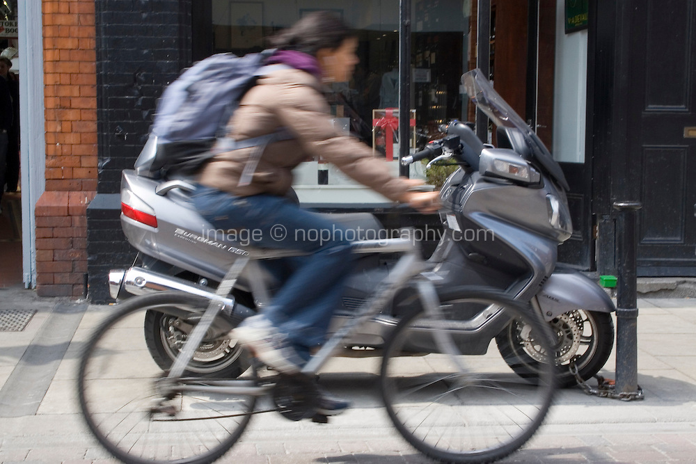 Cyclist speeds past parked moped on Dublin city centre street, Ireland
