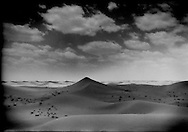 """50 years ago, this was a grassland.  Since Mao's destructive development policies known as the Great Leap Forward (1958 - 1963), Tengger Desert sand mountains 100m (328 ft.) or higher  have swallowed grasslands, lake and farms.  The sand's advance at this point seems unstoppable, Inner Mongolia, China.  Beijing has laid down a line in the desert sand in a stuggle to halt the advance of the Gobi Desert called """"Taming the Yellow Dragon"""" as China's Environmental Agency says that the Gobi Desert expanded 52,400 square km. (20,240 square miles) from 1994 to 1999, about half the size of the state of Pennsylvania."""