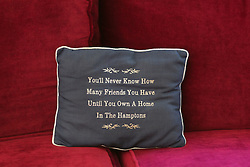 "pillow on a couch, ""you'll never know how many friends you have until you own a home in the hamptons"""