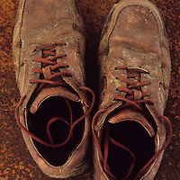 Pair of well-worn brown working or walking boots standing on rusty metal sheet