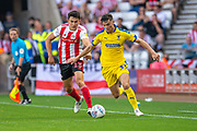Luke O'Nien (#13) of Sunderland AFC tracks back with Callum Reilly (#33) of AFC Wimbledon during the EFL Sky Bet League 1 match between Sunderland and AFC Wimbledon at the Stadium Of Light, Sunderland, England on 24 August 2019.