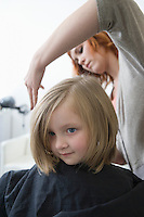 A young girl having her hair cut in the hairdressers