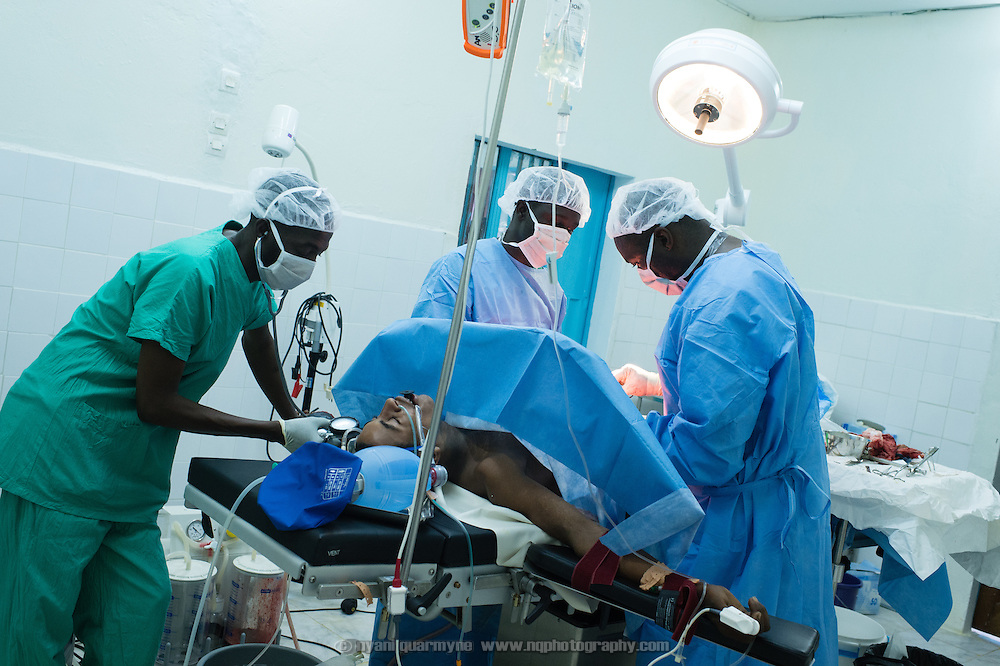 Médecins Sans Frontières (MSF) surgeon, Dr Thotho Kalombo (right), operating on a gunshot victim at the recently completed Médecins Sans Frontières (MSF) surgical unit in Bassikounou, Mauritania on 10 March 2013. Shot twice through the back, the victim required intestinal resection, which was sucessfully performed. Dr Kalombo is assisted by anesthisiologist, Moussa Kondo Kalla (left), and nurse, Ibrahima Ba.