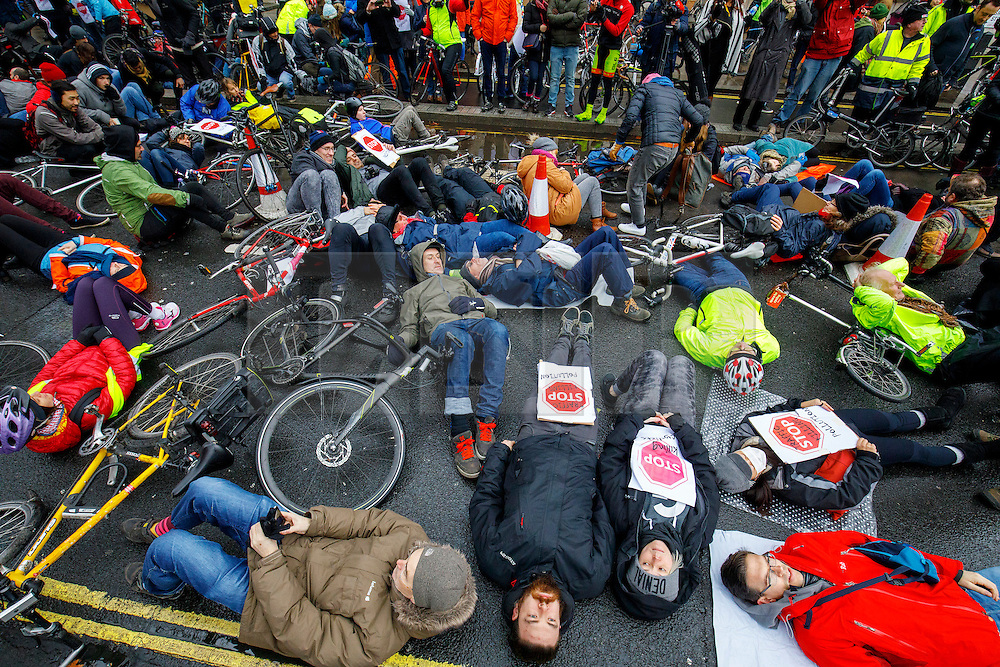 """© Licensed to London News Pictures. 11/02/2017. London, UK. Cyclists hold a """"die-in"""" protest in Westminster, London following the deaths of Anita Szucs, 30 and Karla Roman, 32 both killed while cycling on Monday on the streets of London. Protesters asking for the government to commit to significantly increase funding for cycling and walking starting with 5% of the 2017 transport budget and increasing to 10% by 2020. Photo credit: Tolga Akmen/LNP"""