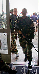01 Sept, 2005. New Orleans, Louisiana.<br /> Thousands of desperate people mass outside the Superdome hoping for a seat on a bus to take them out of town to safety. Members of the Louisiana National guard secure the walkway to the busses from the Superdome.<br /> Photo©; Charlie Varley/varleypix.com