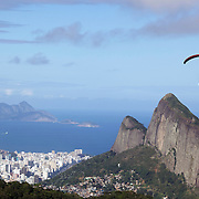 A para glider flying above the hillside of Pedro Bonita high in the hills of Rio de Janeiro. Pilots of hang gliders and para gliders take tourists for tandem flights with breathtaking views of the city before landing on Sao Conrado beach. Rio de Janeiro,  Brazil. 9th September 2010. Photo Tim Clayton.