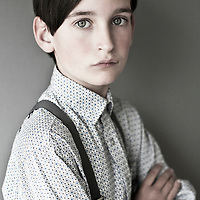 Male youth wearing shirt and braces looking at camera