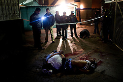 Police secure the scene of a double execution in Mexico City, Mexico.  The two men were blindfolded, handcuffed and shot in the head, in a style that is becoming familiar to Mexicans.  The police believe the killings were part of a low level drug feud. As the borders to the north tighten, more drugs and weapons are staying in Mexico. The rate of addiction is increasing and violent crime is also increasing throughout the country.