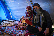 Marwa Hussein and her husband Ahmed Abdul with their newborn baby sit inside a tent in Khazer IDP camp on December 4, 2016.
