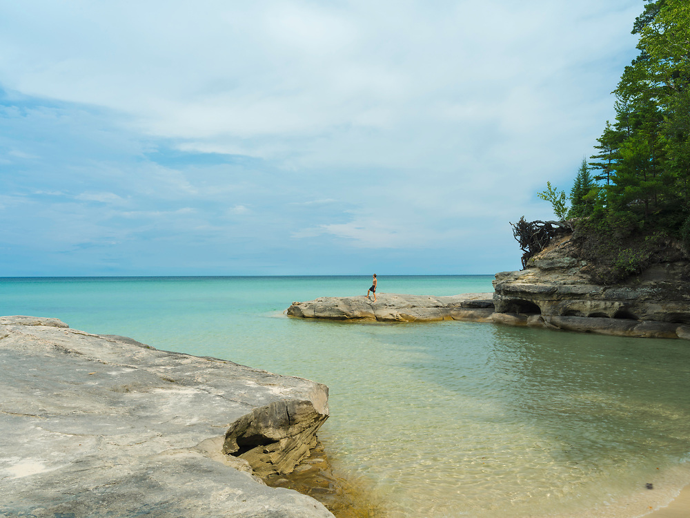 """A boy looking at Lake Superior. Image from the area known as """"The Cove,"""" Pictured Rocks National Lakeshore, Michigan, USA."""