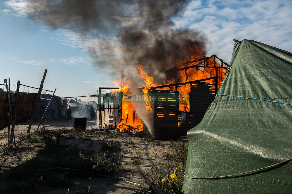 October 25, 2016 - Calais, France - A hut was set o fire during the evection of the Calais Jungle  in Calais, France, on 25 October 2016. Up to the evening, about 4,000 migrants from the Refugee camp on the coast at the English Channel were distributed to several regions in France. The police have begun to tear down the huts and tents in the camp. (Credit Image: © Markus Heine/NurPhoto via ZUMA Press)