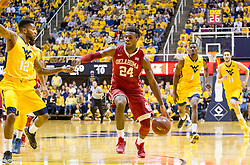 Feb 20, 2016; Morgantown, WV, USA; Oklahoma Sooners guard Buddy Hield (24) dribbles down the lane and is defended by West Virginia Mountaineers guard Tarik Phillip (12) during the first half at the WVU Coliseum. Mandatory Credit: Ben Queen-USA TODAY Sports