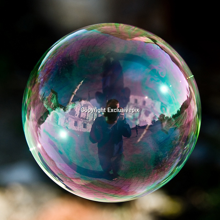 These amazing shots of world famous landmarks are captured through reflection of giant bubbles.<br /> <br /> They say the world is in a bubble, and ace photographer Tom Storm has proved it.These amazing shots of world famous landmarks are captured in a very unusual way  in the oily reflecting of giant bubbles.Tom, from Pennsylvania, said: I wanted people to see the world in a different perspective. The bubble is a shape that is so common around the world and I wanted to see what the world looked like on the side of a bubble. In themselves, they are fleeting, fantastic, and even other-worldly yet so familiar to us all. We can look closely and find momentary reflections, small worlds within these floating orbs that too quickly pass away, never to be seen again. Unless you have a camera. While I was enjoying a street fair in Galway, Ireland in the summer of 2006, bubbles from a nearby vendor floated past me. I saw a reflection in the spheres and quickly took a few shots and moved onto other subjects. When I returned from my trip and reviewed these shots closely I found a whole world in perfect focus. Since that moment I now carry bubble solution with me when I travel. He has been known to pull in crowds watching him take the shots after reeling in friends or even strangers on the spot to actually blow the bubbles. Tom said: People watch and stare as I follow these floating bubbles around with my camera pressed to my eye. Crowds form, and my bubble blowing partners who are either friends or willing strangers do their part to help make sure I dont wander into traffic, for example, while in Times Square in New York City, or into the random passersby. Its photography and is also a great social experiment. Its a show. Its all Natural. No digital manipulation of the bubbles aside from cropping and exposure adjustment. They are all as shot. It takes time, patience, teamwork, and a light-hearted approach. The very act of capturing these reflections is a meditation on virtue. N