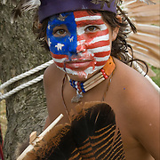 Portrait young Native American with the American flag ( a take off on Captain America ) painted on his face at Thunderbird Pow-Wow in Queens County Farm, New York.<br />