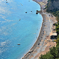 Elevated View of Jazz Beach Near Budva, Montenegro<br /> Judging from its appearance in this elevated view, you'd expect this 4,000 foot beach encircled by gorgeous turquoise water to be called crescent. Instead, it is named Jazz Beach because it is the frequent venue for music festivals and outdoor concerts. The most famous was in 2007 when the Rolling Stones played here during the Bigger Bang Tour.  It is located about two miles west of Budva, Montenegro.