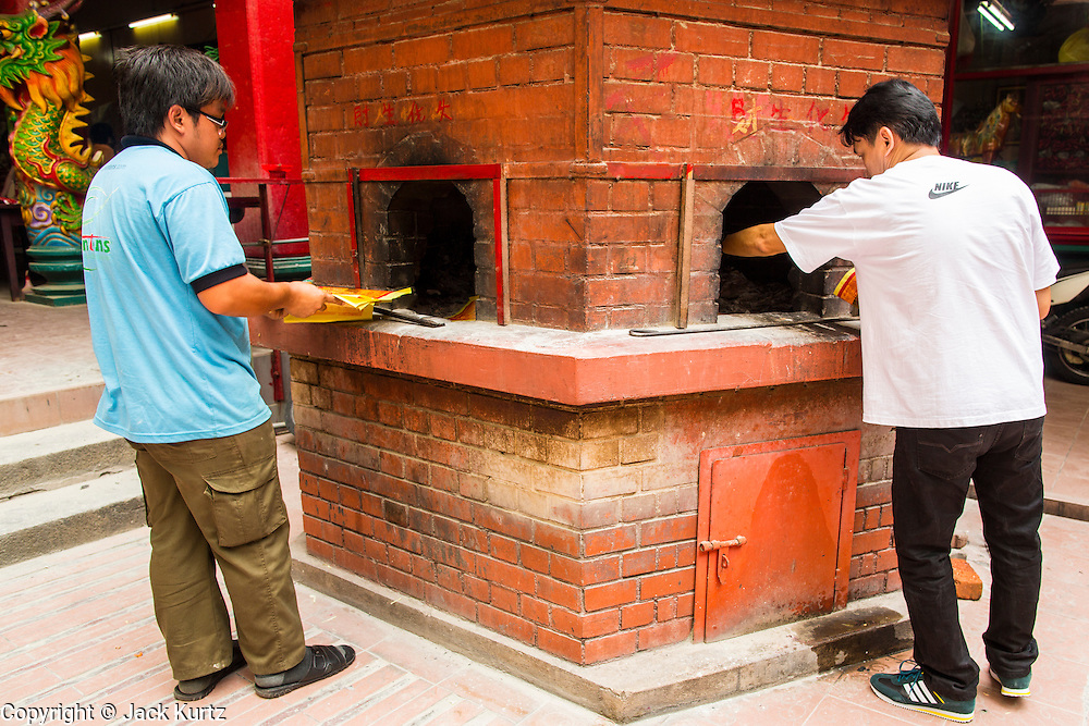 20 DECEMBER 2012 - KUALA LUMPUR, MALAYSIA:  Men burn offerings in a kiln at the Guan Di Temple in Kuala Lumpur, Malaysia. Guan Di Temple (God of War Temple) was built in 1888 and is one of the oldest Chinese Temples in Kuala Lumpur.  PHOTO BY JACK KURTZ