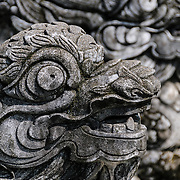 Fierce-looking stone dragons at the foot of stairs at the Imperial City in Hue, Vietnam. A self-enclosed and fortified palace, the complex includes the Purple Forbidden City, which was the inner sanctum of the imperial household, as well as temples, courtyards, gardens, and other buildings. Much of the Imperial City was damaged or destroyed during the Vietnam War. It is now designated as a UNESCO World Heritage site.