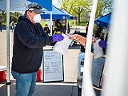 09 MAY 2020 - DES MOINES, IOWA: An artisan cheese maker hands a bag of cheeses to a customer in a drive through farmers' market in Des Moines. The Governor allowed farmers' markets across the state to reopen last weekend, but limited them to selling just food stuffs. They are not allowed to have entertainment or sell non-food items. Most farmers' markets in Iowa are taking a wait and see approach to reopening. The Downtown Farmers Market in Des Moines announced they won't reopen until July. Three vendors set up their own drive through farmers' market in the parking lot of Des Moines theatre Saturday. Hundreds of people got in line to buy fresh produce and artisan cheese. More than 11,670 people have tested positive for COVID-19 in Iowa and more than 250 have died from the disease.           PHOTO BY JACK KURTZ