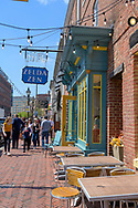 Fells Point, Baltimore, MD, USA -- April 13, 2019. Tourists and shoppers walk along Thames St in historic Fells Point, Baltimore.