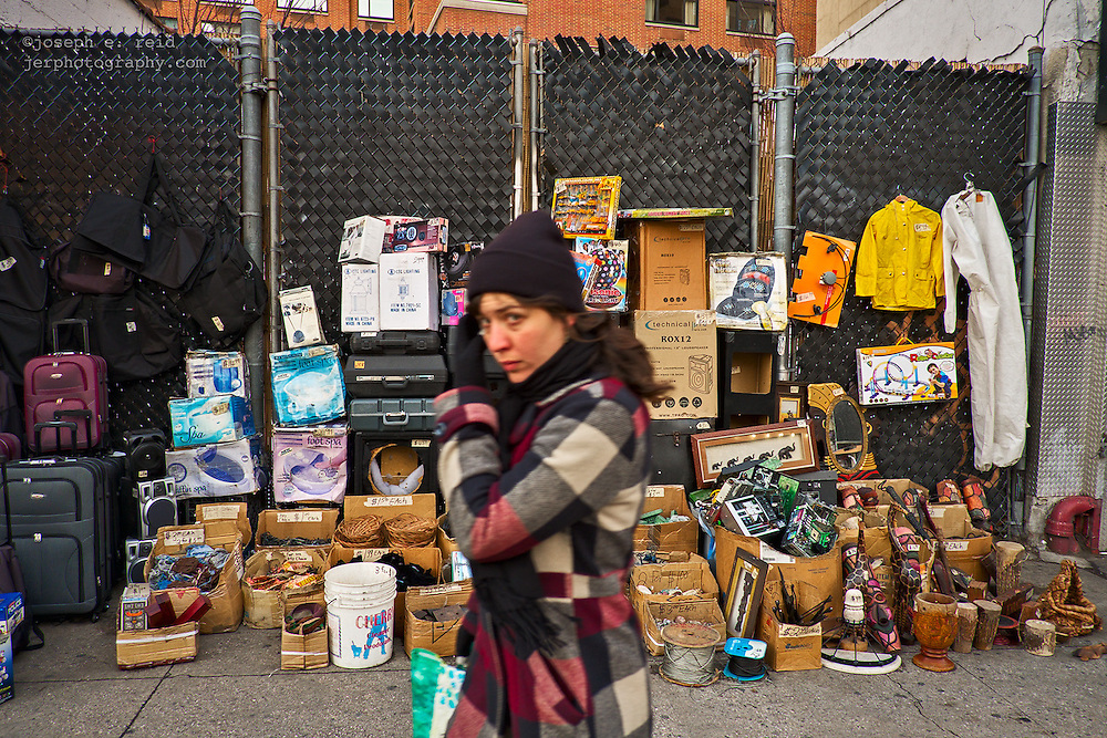 Woman passing used items for sale on Canal Street, New York, NY, US