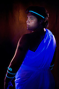 Young woman wearing a glowing toga, headband and wrist cuffs.Black light