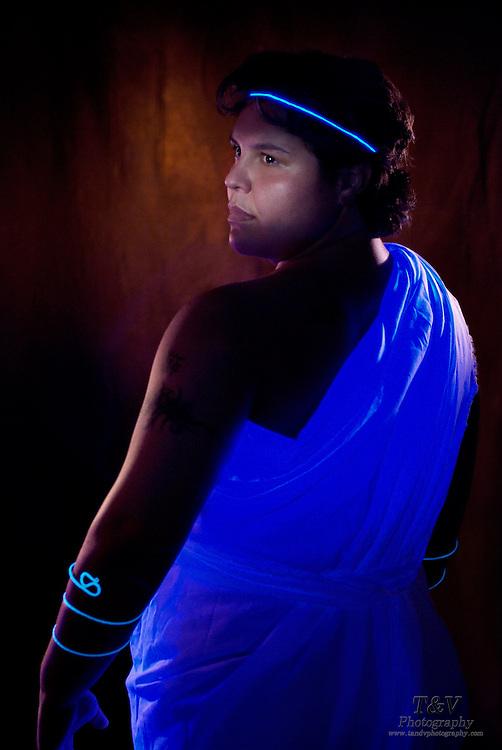 Young woman wearing a glowing toga, headband and wrist cuffs.Black light
