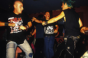 A group of punks with shaved head, mohican and dyed blue hair dance in club, U.K, 1990s.