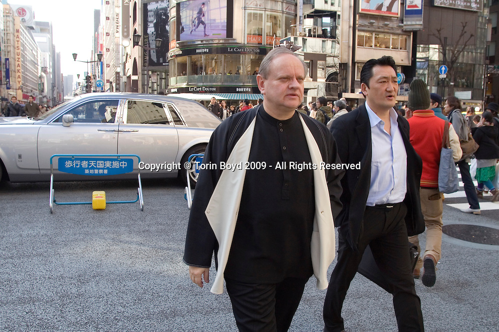 "This is world renowned chef Joel Robuchon visiting Tokyo's Ginza district on February 7, 2009. The Rolls Royce in the background is his limousine and the Japanese man along side him (jacket, unbuttoned white shirt, briefcase) is Mitsugu Yasuda who's closely assisting Robuchon during his stay in Japan. Robuchon was in town to attend an international food exposition called ""2009 Tokyo Taste"". This three day event from February 9-11, 2009 showcases some of the world's most famous chefs including Robuchon and Ferran Adria (of El Bulli) who are both Honorary Advisors to this event. Other chefs participating in this event are Heston Blumenthal, Pierre Gagnaire, Jacques Puisais, Bruno Menard, Herve This, Ferran Adria, and Nobuyuki Matsuhisa to name a few. Robuchon has restaurants in Tokyo and Nagoya Japan including; L'Atelier de Joel Robuchon and Le Cafe Joel Robuchon. These establishments are connected with Four Seeds Corporation, a Japanese corporation that owns and operates several popular restaurant chains around Japan."