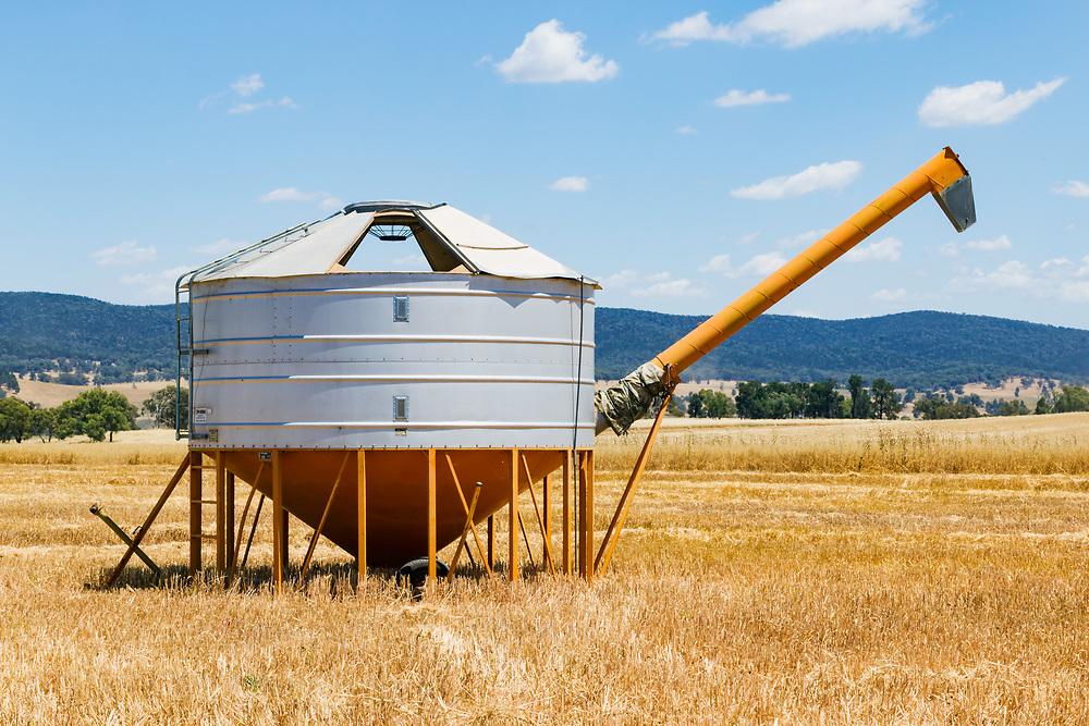 Mobile field bin grain silos in paddock after wheat harvest near Toogong, New South Wales, Australia