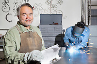 Portrait of a happy mature man with young male welding in background
