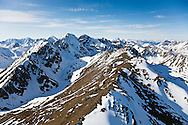 Longer days and warmer temperatures in spring begin to expose the seemingly endless ridgelines of the snow covered Chugach Mountains in Chugach State Park near Anchorage in  Southcentral Alaska. Morning.