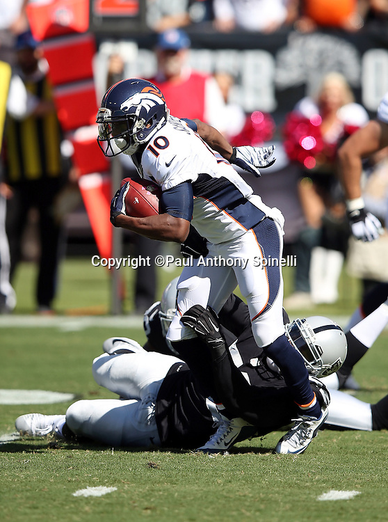 Denver Broncos wide receiver Emmanuel Sanders (10) gets hit by Oakland Raiders defensive end Khalil Mack (52) after catching a pass during the 2015 NFL week 5 regular season football game against the Oakland Raiders on Sunday, Oct. 11, 2015 in Oakland, Calif. The Broncos won the game 16-10. (©Paul Anthony Spinelli)