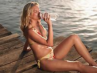 Young woman in bikini sitting on jetty drinking water
