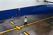 A British Airways security guard patrols beneath fuselage of a Boeing 747 parked on the apron at Heathrow's Terminal 5..