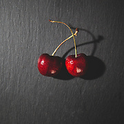 Two cherries on a slate board, in studio, dark food photography