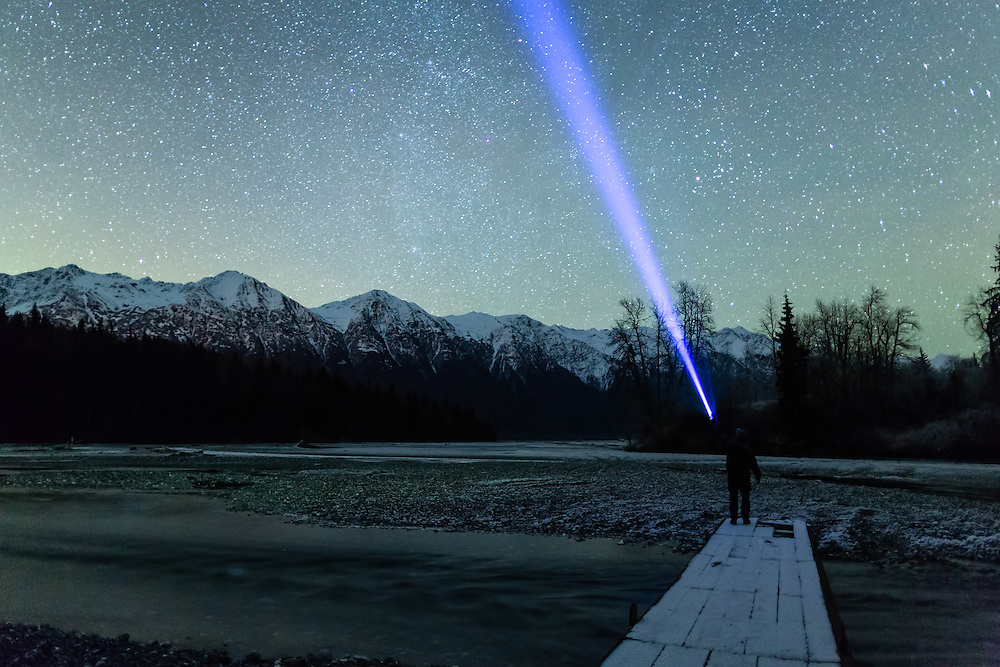 Man pointing flashlight toward the night sky along the Chilkat River in the Chilkat Bald Eagle Preserve near Haines in Southeast Alaska. Winter. Evening. MR.