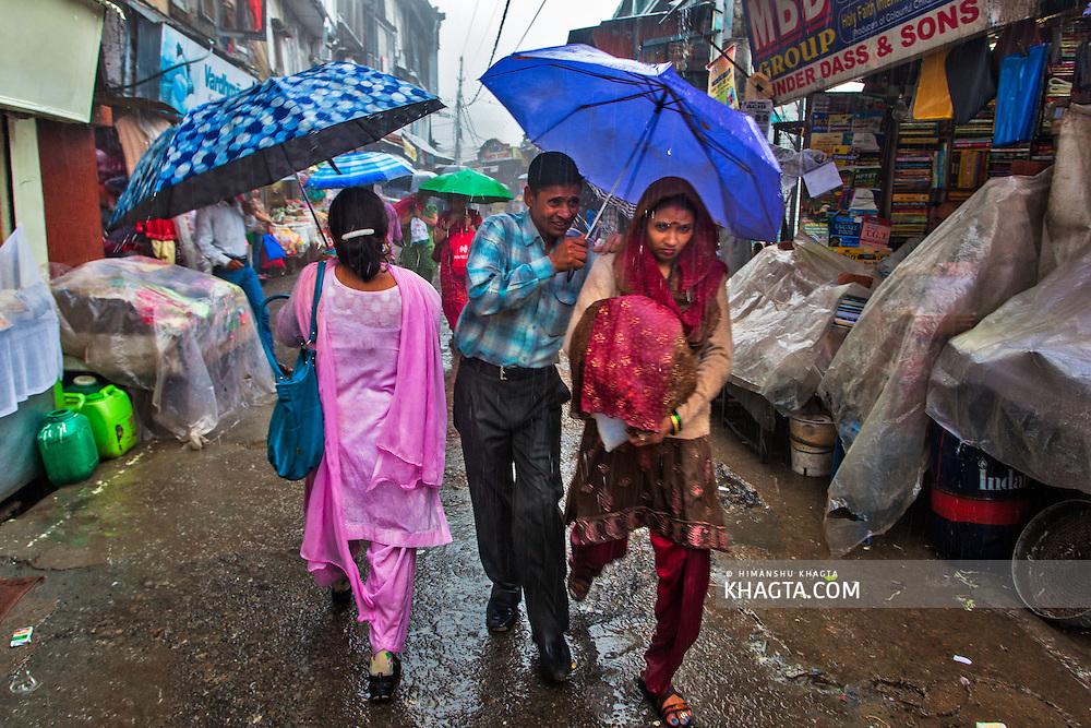 People walking in lower bazaar of Shimla in heavy rainfall.
