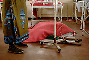 Howard Hospital, Zimbabwe. December 12, 2008. A woman in her late twenties or early thirties lies on the hospital floor recovering from a spontaneous abortion. She was transfered from a bed.